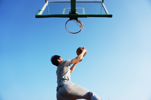 Get-your-family-fit-man-shooting-ball-at-basketball-hoop